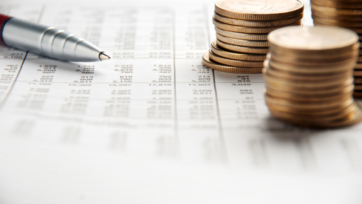 Pen and coins pile on a financial report